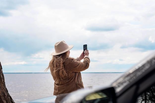 Средний снимок женщины, делающей фотографии