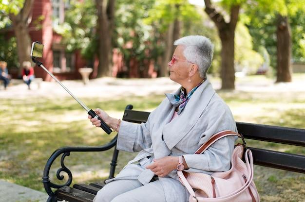 公園で自撮りをするミディアムショットの女性