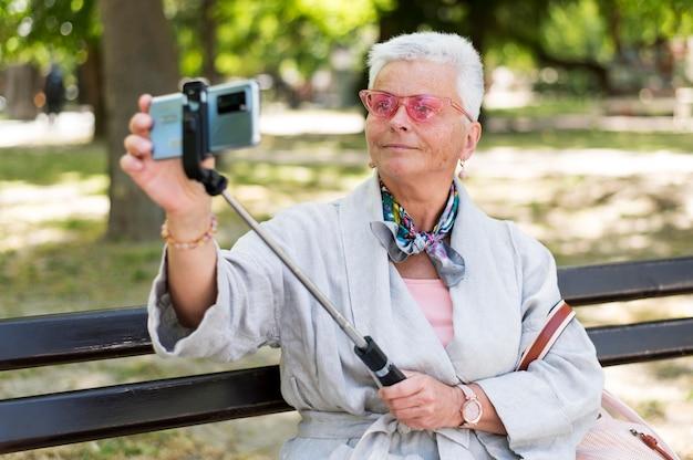 ベンチで自撮りをするミディアムショットの女性