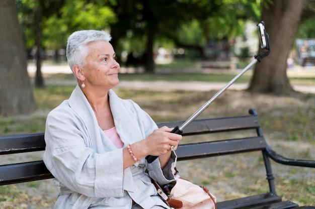 屋外で自撮りをするミディアムショットの女性