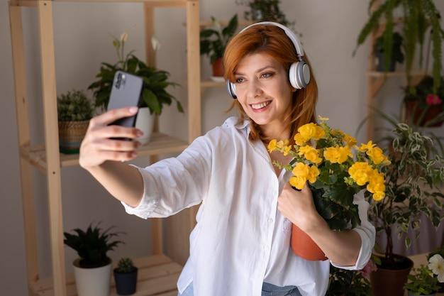 花とセルフィーを取るミディアムショットの女性