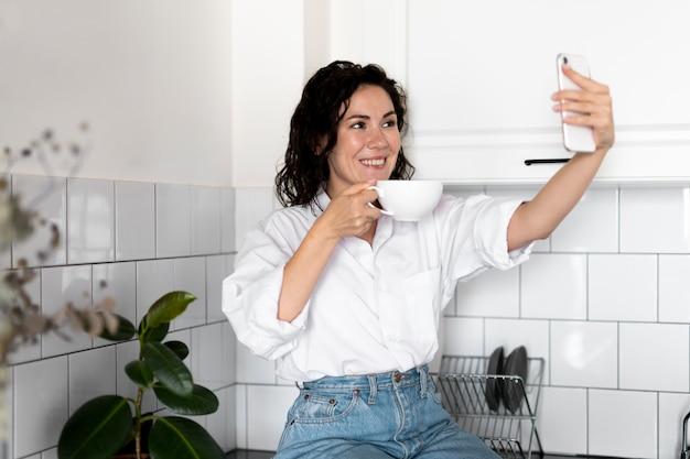 Средний снимок женщины, делающей селфи