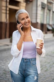 Женщина среднего выстрела разговаривает по телефону