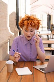 電話で話しているミディアムショットの女性