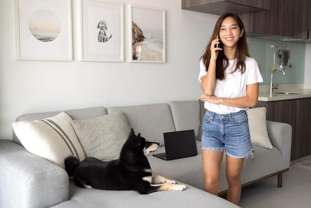 Donna del tiro medio che parla al telefono a casa