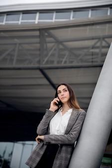 Donna del tiro medio che parla al telefono