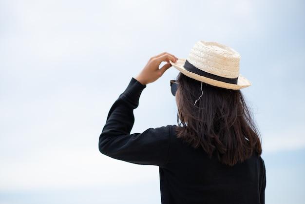 ミディアムショットの女性の日焼けした肌は、黒いシャツとサングラスのホールドの麦わら帽子をかぶっています。海を見ています。海の背景に。夏の旅行。
