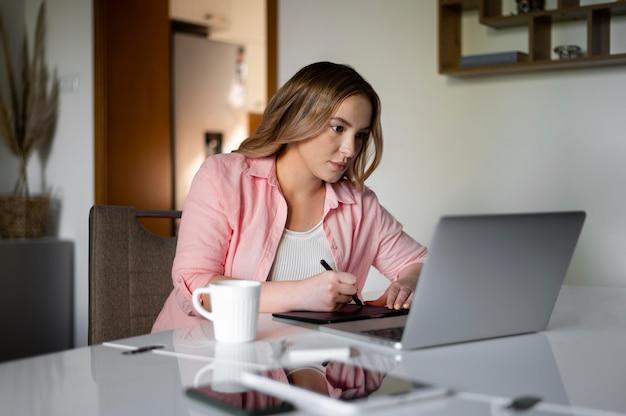 Medium shot woman teleworking