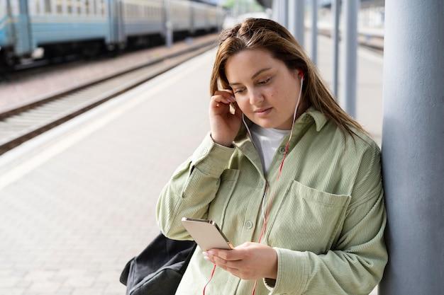 Donna del tiro medio alla stazione dei treni