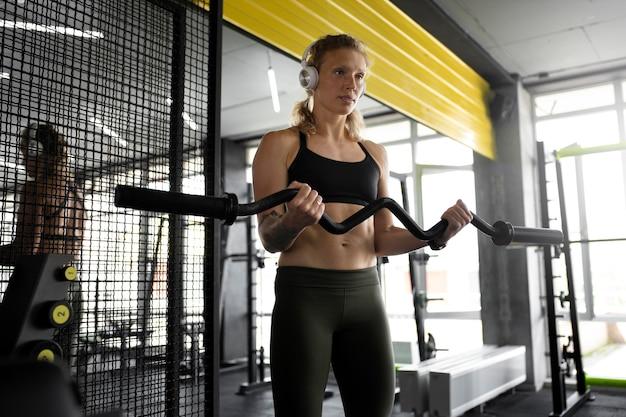 Средний выстрел женщина тренирует оружие