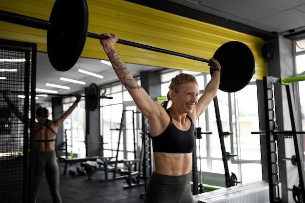 ダンベルでトレーニングするミディアムショットの女性
