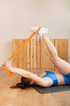 Тренировка женщины среднего размера с резинкой