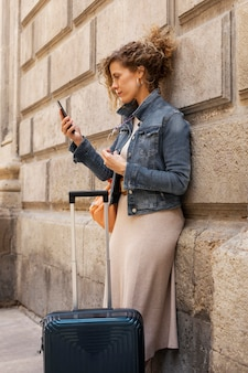 手荷物を持って旅行するミディアムショットの女性