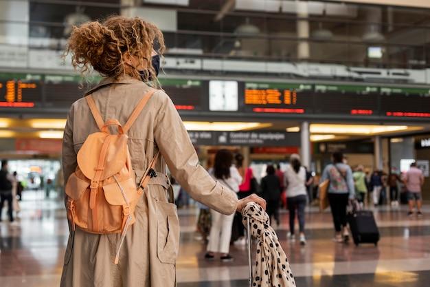 マスクを持って旅行するミディアムショットの女性