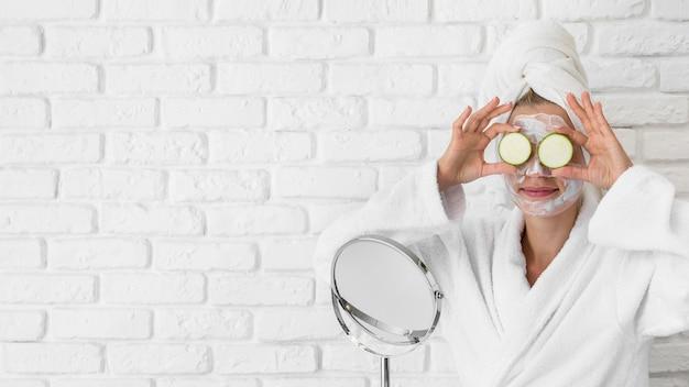 Donna del colpo medio che prova il trattamento del viso