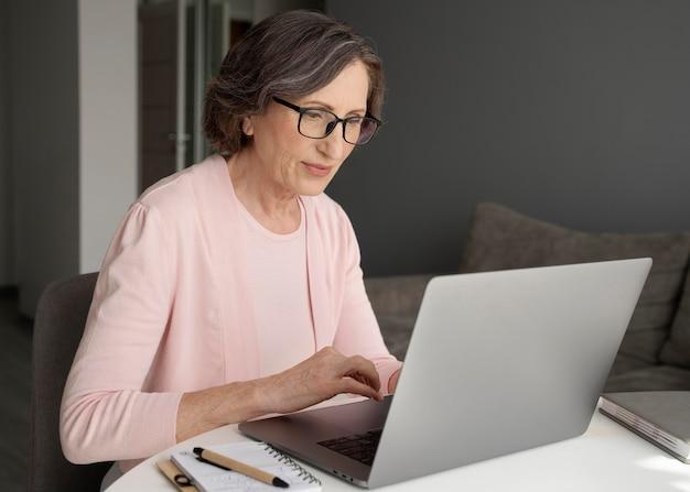 Donna del colpo medio che digita sul computer portatile