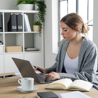 Женщина среднего выстрела, печатающая на клавиатуре