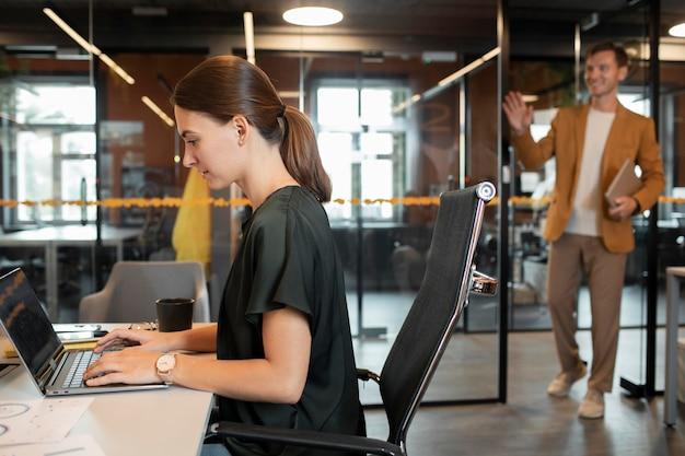 ノートパソコンで入力するミディアムショットの女性