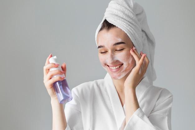 얼굴 제품을 사용하는 중진공 상태 샷 여자