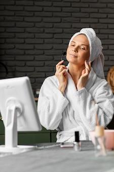Donna di colpo medio utilizzando strumento facciale