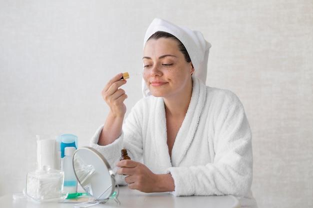 Colpo medio donna che utilizza siero