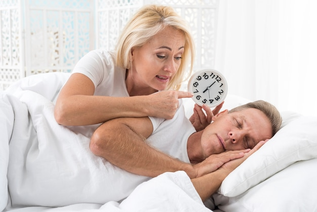 Medium shot woman waking up man