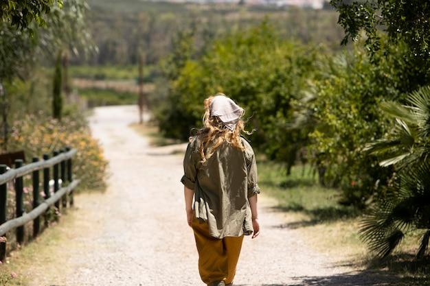 야외에서 걷는 미디엄 샷 여성