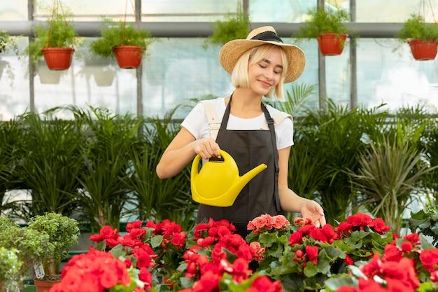 Женщина среднего выстрела, поливающая цветы