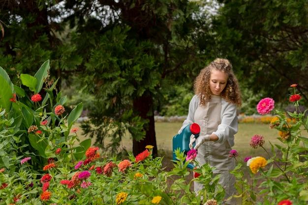 Donna di tiro medio che innaffia i fiori
