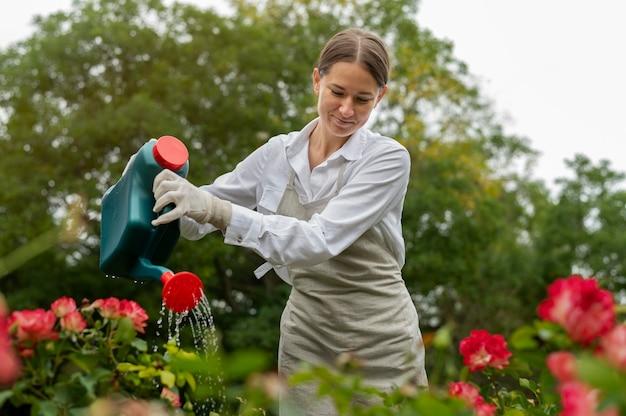 꽃에 물을 주는 중형 여성