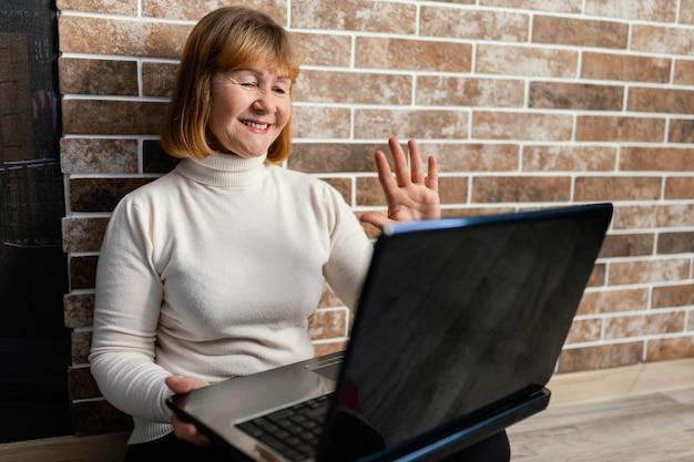 ノートパソコンで手を振っているミディアムショットの女性