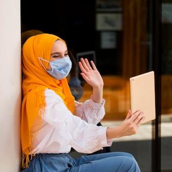 Medium shot woman waving at tablet