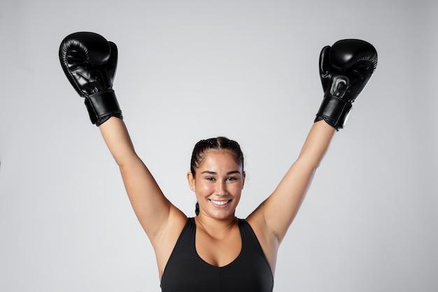 Donna del tiro medio che indossa guanti da boxe