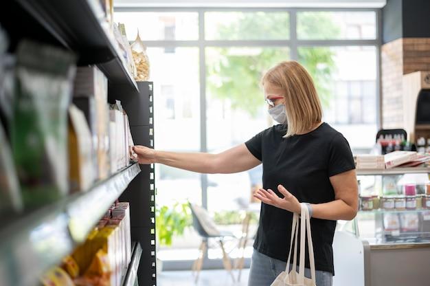 Donna del tiro medio che indossa la maschera facciale in negozio