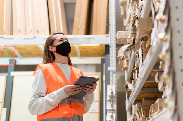 仕事でマスクを身に着けているミディアムショットの女性