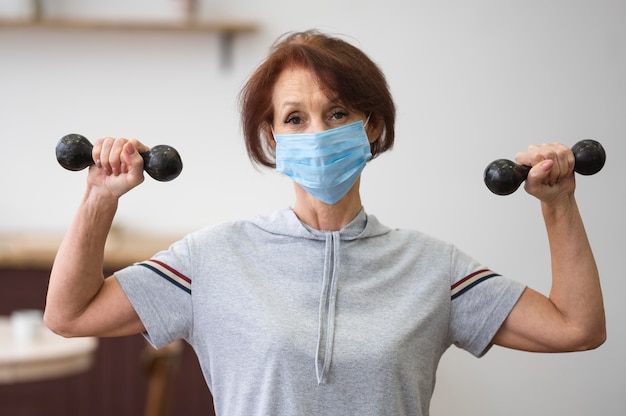 Colpo medio donna che indossa maschera medica