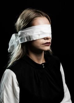 Medium shot of woman wearing white blindfold