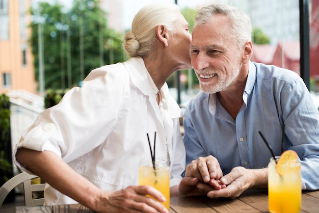 Medium shot woman whispering in man's ear