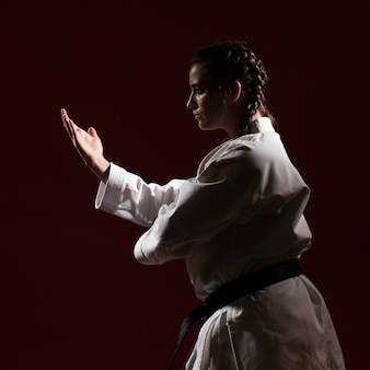 Medium shot of woman in white karate uniform