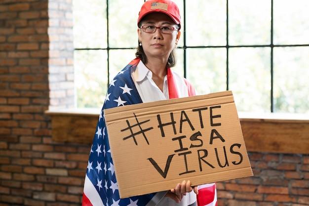 Среднего плана женщина с американским флагом и плакатом