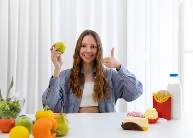 Medium shot woman with apple and thumb up