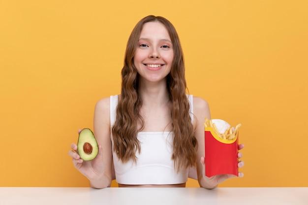 Donna a tiro medio con avocado e patatine fritte