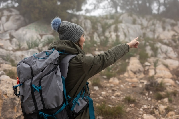 Medium shot woman with backpack in nature