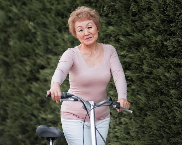 Женщина среднего выстрела с велосипедом на открытом воздухе