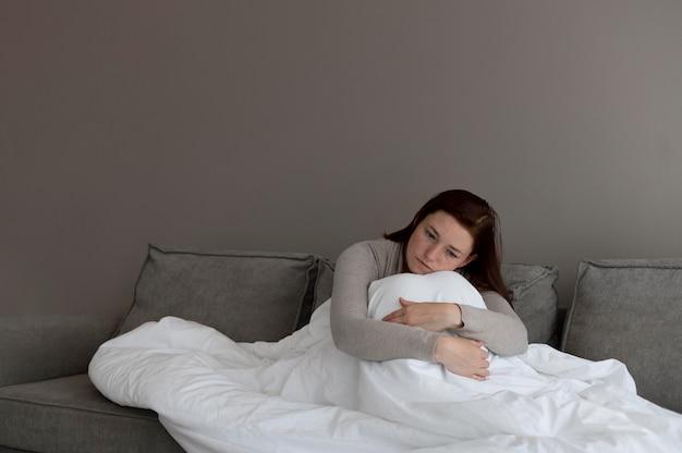 Среднего выстрела женщина с одеялом