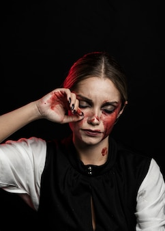 Medium shot of woman with bloody makeup