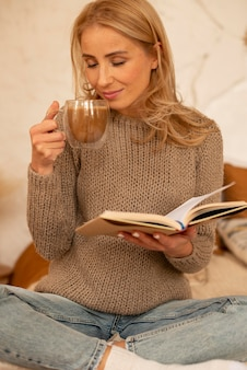 本と飲み物を持つミディアムショットの女性