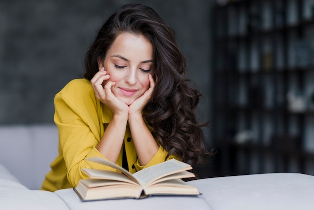 Medium shot woman with book indoors