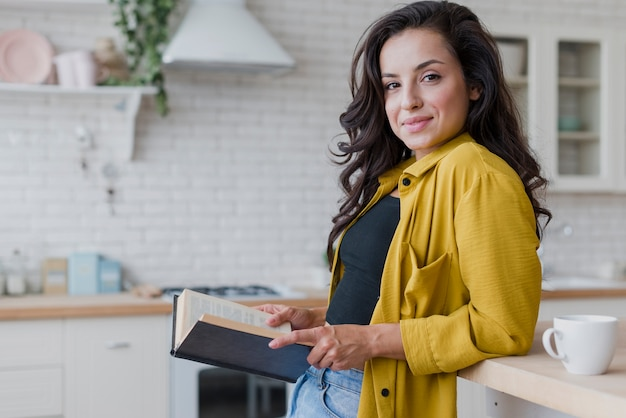 Medium shot woman with book in the kitchen