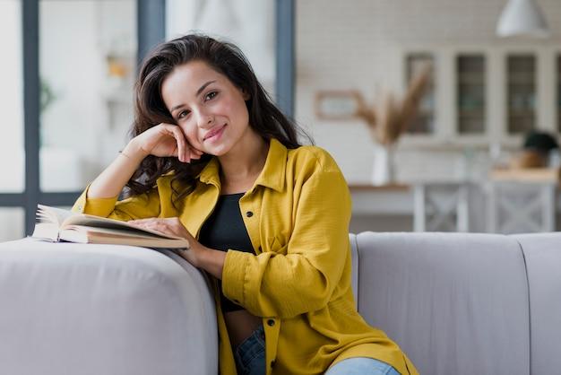 Medium shot woman with book looking at camera
